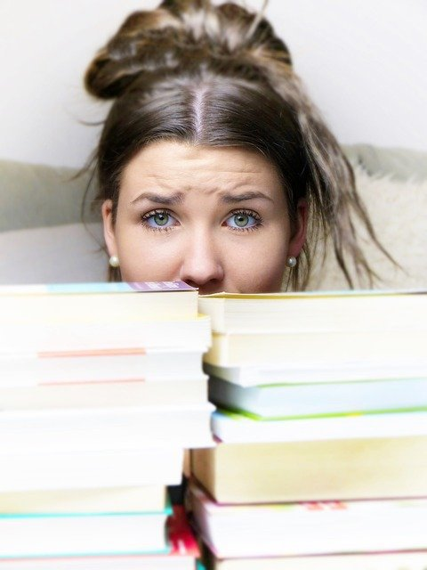worried woman behind books