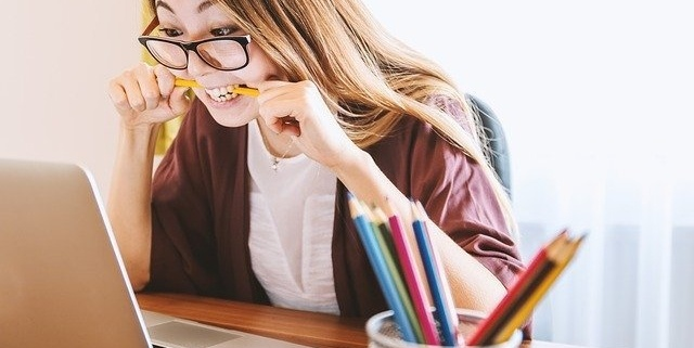 student looking at laptop chewing pencil